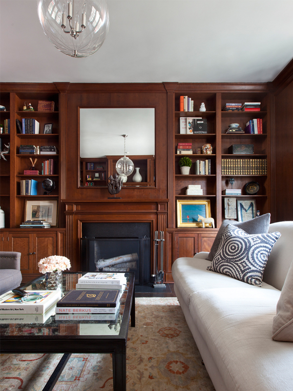 wood paneled library with glass pendant