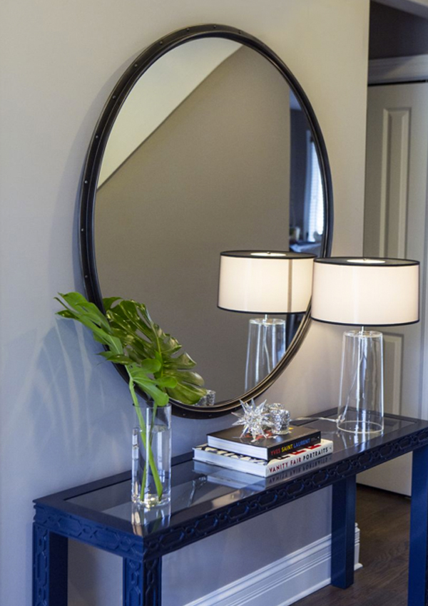 entry with large round mirror and navy lacquer console